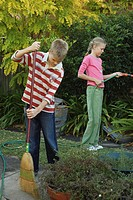 Boy (10-12) sweeping path, twin sister using garden hose