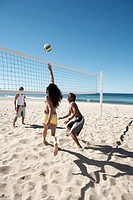 Teenage girl and two boys (15-17) playing volley ball on beach