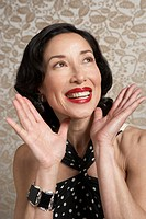 Mature woman smiling and gesturing, looking up