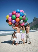 Group of people on beach with beach balls