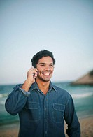 Man on beach using mobile phone, smiling