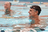 Two mature men in laned swimming pool, smiling, close-up
