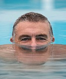Mature man in pool, head half submerged in water, portrait, close-up