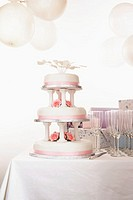Wedding cake on table by champagne glasses
