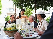Bride standing by family at table outdoors, smiling