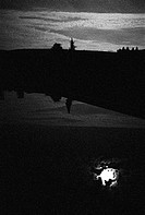 Dark landscape with moon reflected in water