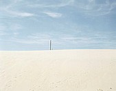 Pole in distance on sand