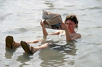 Woman tourist reading newspaper during a bath. Dead Sea. Jordan.