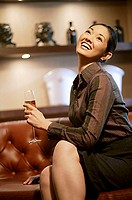 Woman with champagne glass, legs crossed, looking up, smiling