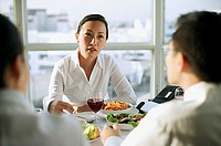 Businesswoman facing other executives over lunch table