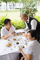 Couple in restaurant, man handing payment to waiter