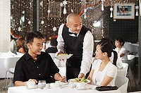 Waiter serving couple at restaurant