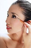 Woman applying mascara, looking away