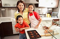 Mother and two daughters in kitchen, looking at camera