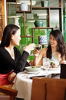 Two women eating in restaurant, toasting with drinks