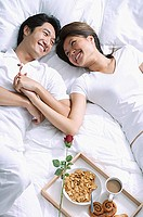 Couple lying on bed, holding hands, breakfast on tray next to them