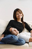 Couple on sofa, man lying on woman´s lap, both smiling at camera
