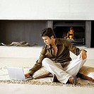 young man sitting on the floor working on a laptop