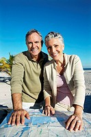 portrait of a mature couple on a beach reading a map