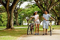 Couple walking in park, holding bicycles