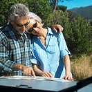 mature couple standing together reading a map