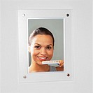reflection in a mirror of a woman comparing her teeth to a scale of whiteness