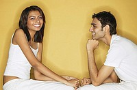 Couple sitting face to face, woman looking at camera, man looking at her