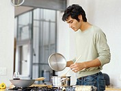 side profile of a young man cooking food in the kitchen