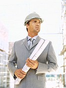 close-up of an architect holding blueprints at a construction site