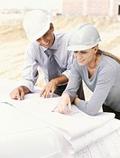 high angle view of two architects looking at blueprints at a construction site
