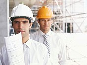 portrait of two architects wearing hardhats at a construction site