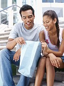 young couple looking in a shopping bag