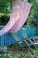 Deckchairs and a mosquito net in an autumnal garden (thumbnail)