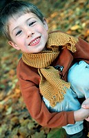 Little boy in the autumnal wood, forest, squatting on the ground