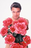 Portrait of a young man, 20-25 25-30 30-35 years old, dark-haired, masculine and beautiful, offering a bouquet of red roses