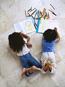 high angle view of two girls coloring with crayons