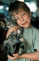 A little boy, 5-10 years old, holding a cat