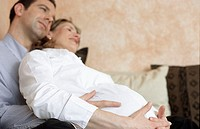 A young couple, young man and young pregnant woman, 25-30 30-35 35-40 years old, sitting on the sofa (thumbnail)