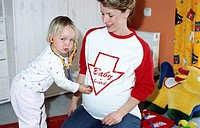A young pregnant mother, woman, 25-30 30-35 35-40 years old, playing with her little daughter (thumbnail)