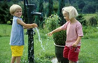 Two children, little boy, little girl, 5-10 years old, playing in the garden with water