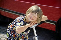 A little girl, 5-10 years old, with a pedal-scooter in front of a car