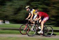 Two young men 15-20 20-25 25-30 years old, sportsmen, bikers, cyclists, cycling outside in summer