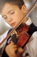 A boy, 5-10 years old, playing a violin