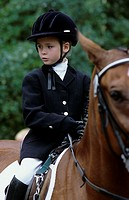 A little girl, 5-10 years old, riding a horse at a horse show (thumbnail)