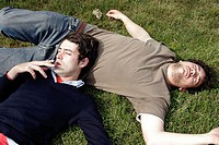 Two young men resting on grass