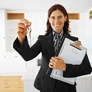 Young businesswoman holding out a set of keys (blurred)