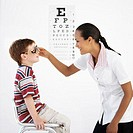 Side profile of a female optometrist examining a boy´s (8-10) eyes