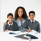 Portrait of a young woman helping her teenage children (11-13) with homework