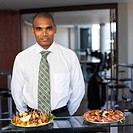 front view portrait of a businessman standing and two plates of finger food on table