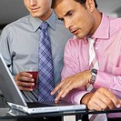 close up of two businessmen holding a glass working on the laptop